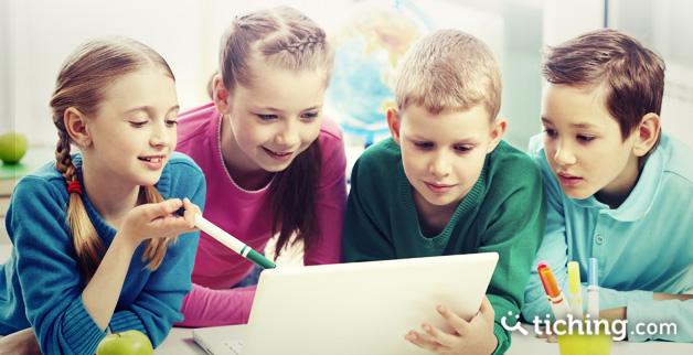 Imagen del artículo aprendizaje cooperativo: 4 niños trabajando en equipo en un mismo ordenador.