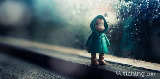 imagen artículo acoso escolar: muñeco triste al lado de una ventana con gotas de lluvia