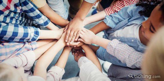 Imagen para el artículo 7 dinámicas para formar grupos: manos de niños al centro simbolizando el trabajo en equipo.