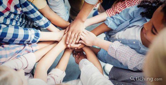Imagen: niños con las manos al centro simbolizando el trabajo el equipo