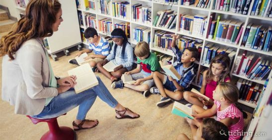 Imagen: profesora y niños sentados en la biblioteca promocionando la lectura