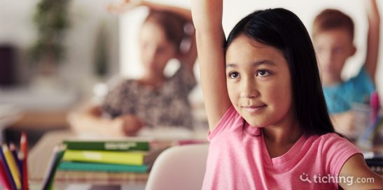 niña levantando la mano y focalizando la atención en el docente