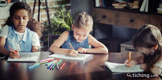 niñas sentadas en una mesa pintando los mandalas proporcionados por la maestra