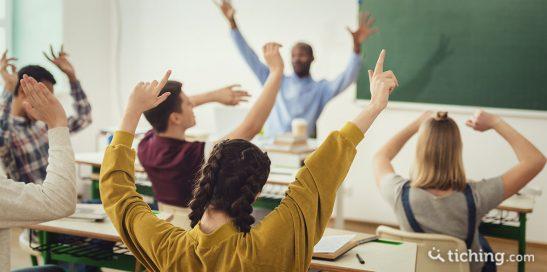 Imagen del artículo una metodología basada en la realidad de los jóvenes: adolescentes en clase con las manos levantadas