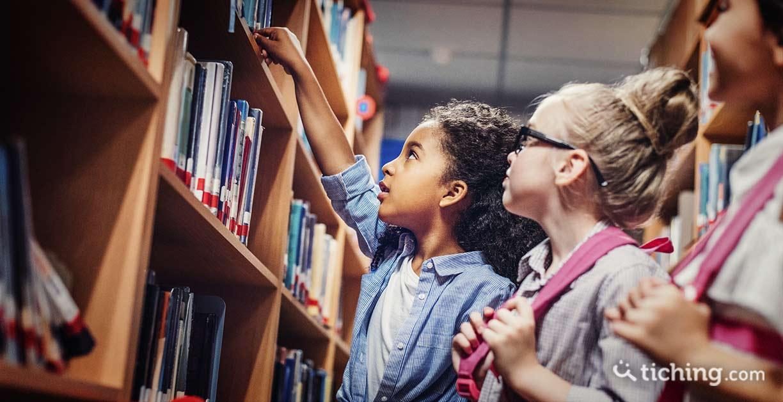 Imagen: niña escogiendo libros en la biblioteca escolar