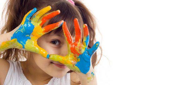 Niña jugando con colores para ilustrar los beneficios de las actividades plásticas