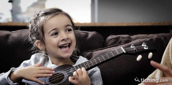 Niña con una guitarra para ilustrar las 8 razones para aprender música desde pequeños