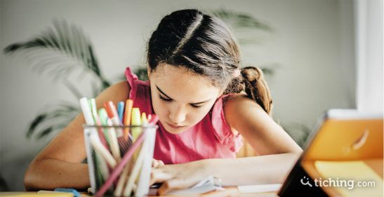 Niña en una autoevaluación escribiendo en una mesa junto a una tablet