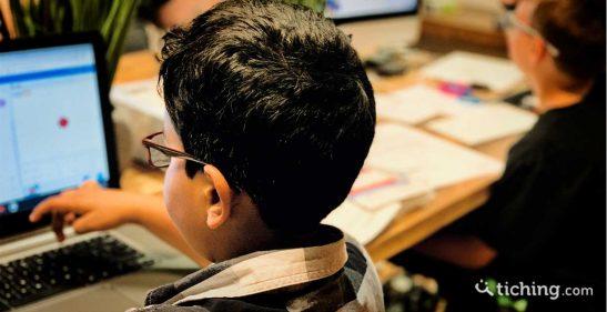Niños en el aula con ordenadores y papel para ilustrar la autonomía y autorregulación